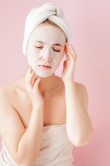 아름 다운 젊은 여자는 분홍색에 얼굴에 화장품 티슈 마스크를 적용합니다