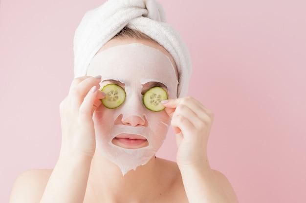 아름 다운 젊은 여자는 분홍색 배경에 오이 얼굴에 화장품 티슈 마스크를 적용합니다. 건강 관리 및 미용 치료 및 기술 개념