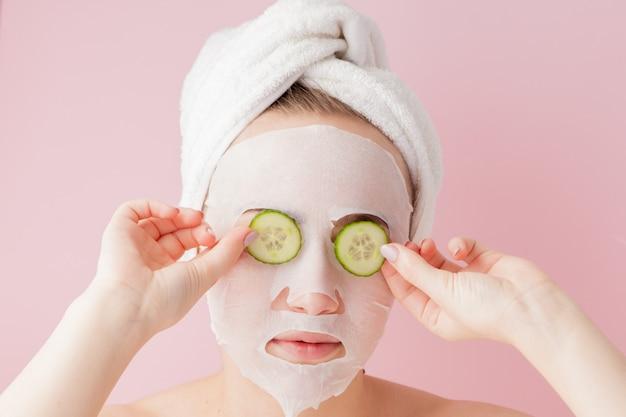 아름 다운 젊은 여자는 분홍색 배경에 오이 얼굴에 화장품 티슈 마스크를 적용합니다.