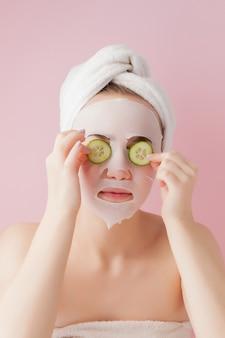 美しい若い女性は、ピンクの壁にキュウリが付いている顔に化粧ティッシュマスクを適用しています。ヘルスケアと美容トリートメントとテクノロジーのコンセプト。