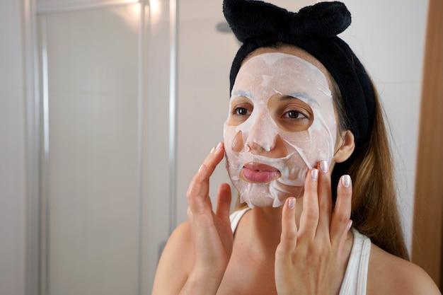 아름다운 젊은 여성이 욕실에서 화장용 티슈 마스크를 얼굴에 바르고 있습니다. 건강 관리 및 미용 치료 개념입니다.