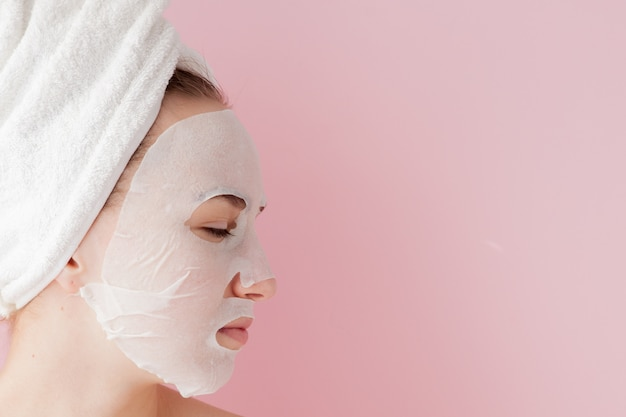 Beautiful young woman is applying a cosmetic tissue mask on a face on pink