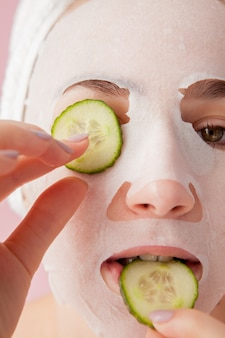 Beautiful young woman is applying a cosmetic tissue mask on a face with cucumber on pink