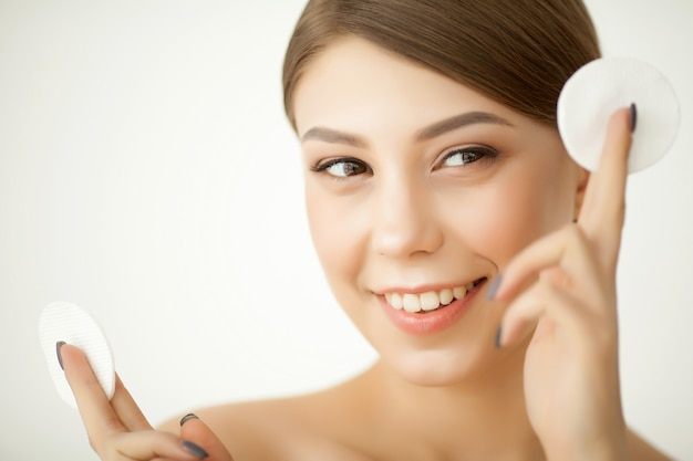 Beautiful young woman is cleaning her face