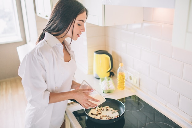 Beautiful young woman is cooking breakfast.