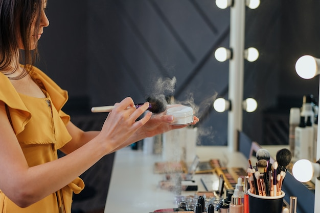 Beautiful young woman is doing makeup using a powder while looking at the mirror