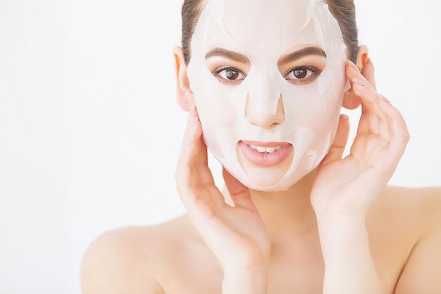 美しい若い女性は、キュウリと目で横になっているスパで顔の粘土マスクを取得しています