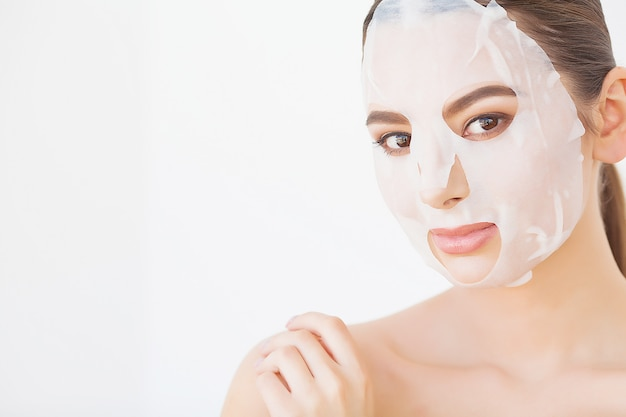 Beautiful young woman is getting facial clay mask at spa, lying with cucumbers on eyes