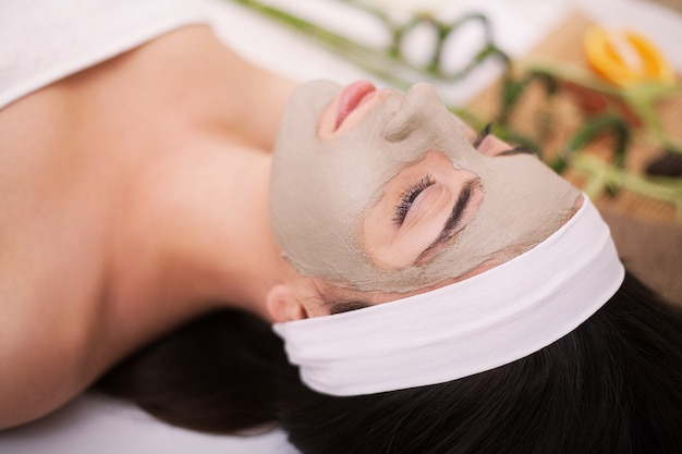 Beautiful young woman is getting facial clay mask at spa