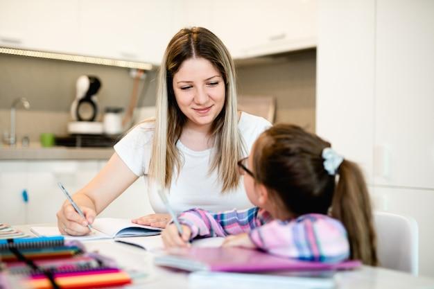 美しい若い女性が妹の宿題を手伝っています。
