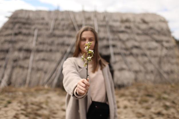 美しい若い女性は、古いわらの家の背景に開花枝を保持しています