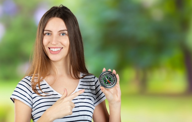 Beautiful young woman is holding a compass near her face.