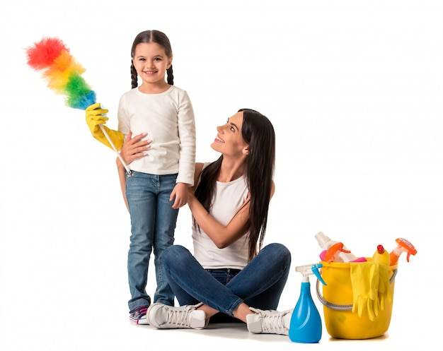 Beautiful young woman is holding detergents and duster