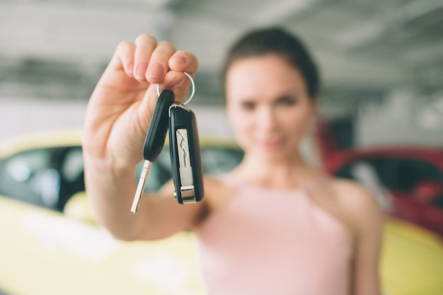 Beautiful young woman is holding a key in car dealership