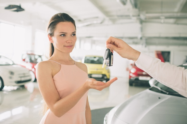 Beautiful young woman is holding a key in car dealership.