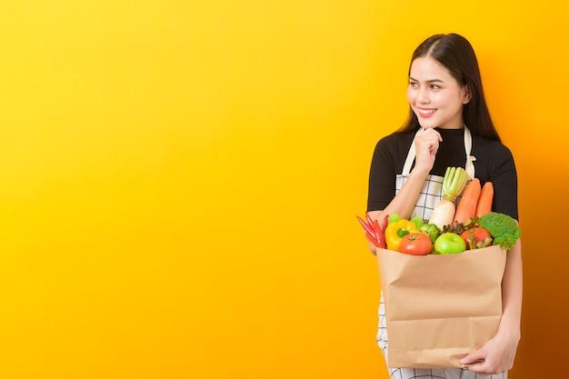 食料品の袋の黄色の壁に美しい若い女性が野菜を持っています。