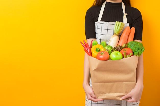 Красивая молодая женщина держит овощи в продуктовой сумке желтой стене