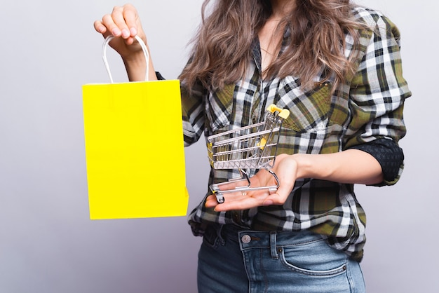 Beautiful young woman is holding a yellow shopping bag and a trolley on white.