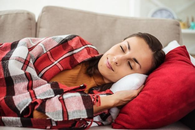Красивая молодая женщина лежит на диване
