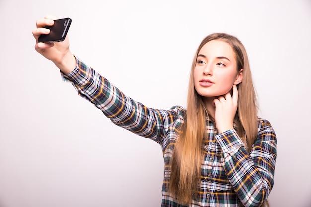 Красивая молодая женщина делает селфи фото со смартфоном, изолированным на белой стене