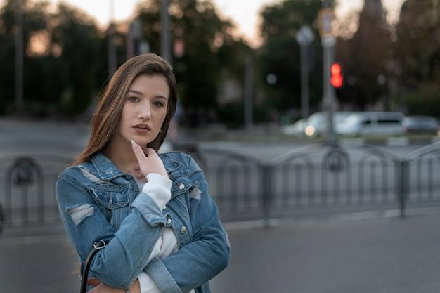 美しい若い女性が道路でポーズをとっています。都市の背景に学生の肖像画。夕方の散歩。