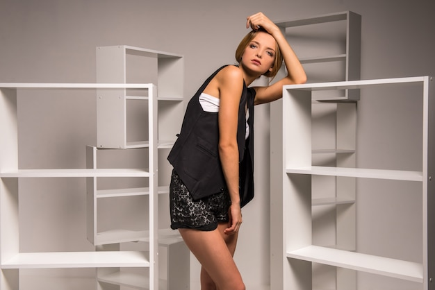 Beautiful young woman is posing with empty shelves.