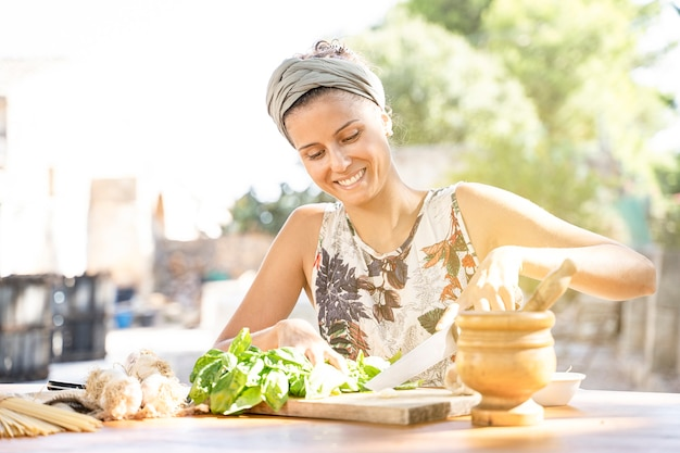 Beautiful young woman is preparing lunch in the outdoor kitchen. healthy food. vegan- dieting concept. healthy lifestyle. cooking at home. prepare food. cutting ingredients on table