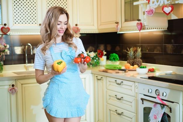 美しい若い女性がキッチンで野菜サラダを準備しています。
