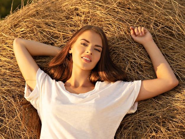 美しい若い女性は干し草の山でリラックスしています。美しいセクシーな女の子は自然にあります。長い茶色の髪の幸せなブルネットの少女。自然のかわいいモデルの肖像画。リラックスした夏の時間。