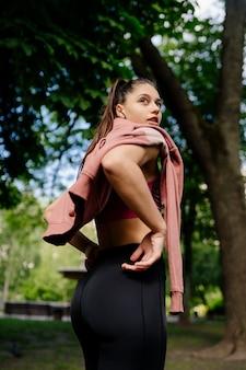 美しい若い女性は公園でジョギングした後休んでいます。