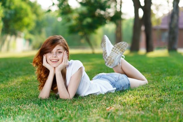 美しい若い女性は新鮮な緑の芝生で休んでいます。
