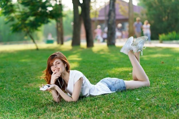Красивая молодая женщина отдыхает в свежей зеленой траве