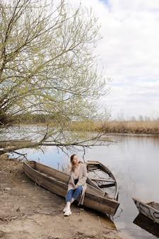 美しい若い女性が座っていると春の日に川の近くのボートで楽しんでいます。