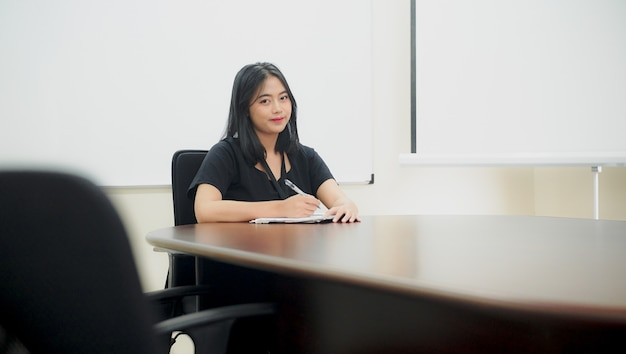 Beautiful young woman is sitting on a chair and ready to write event activities in the office