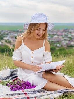 美しい若い女性が牧草地に座って本を読んでいます