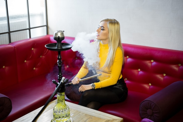 A beautiful young woman is sitting on a red leather sofa and smoking a hookah.