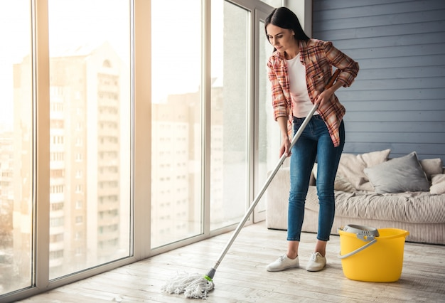 Beautiful young woman is smiling while cleaning floor