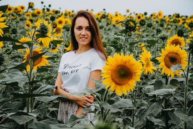 Beautiful young woman is standing in blooming sunflowers looking