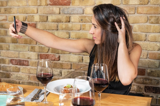 Beautiful young woman is taking a selfie photograph while eating in restaurant.