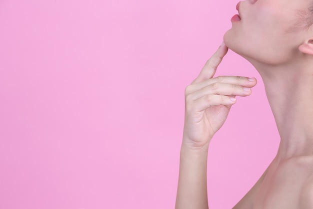 Beautiful young woman is touching her chin with her index finger on pink wall.