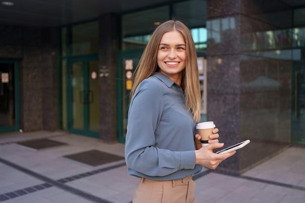 美しい若い女性は彼女のスマートフォンデバイスのアプリを使用してビジネスの建物の近くにテキストメッセージを送信しています