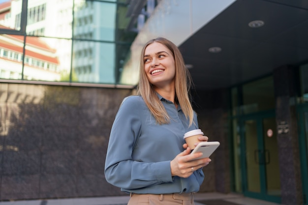 아름 다운 젊은 여자가 그녀의 스마트 폰 장치에서 앱을 사용하여 비즈니스 건물 근처에서 문자 메시지를 보내고 있습니다.