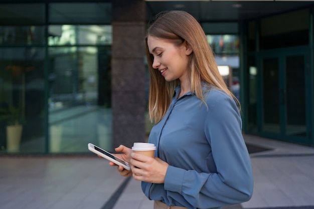 Beautiful young woman is using an app in her smartphone device to send a text message near business buildings