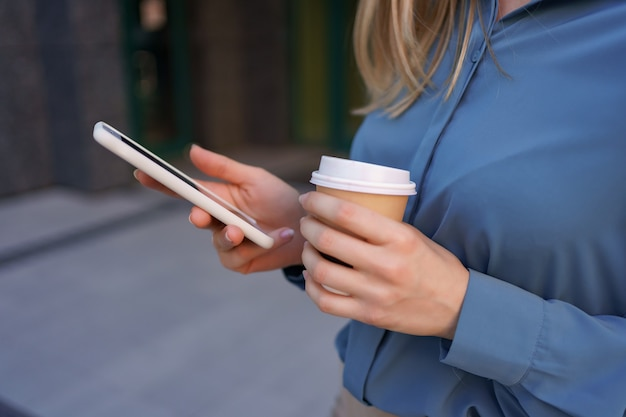 Bella giovane donna sta utilizzando un'app nel suo dispositivo smartphone per inviare un messaggio di testo vicino a edifici commerciali