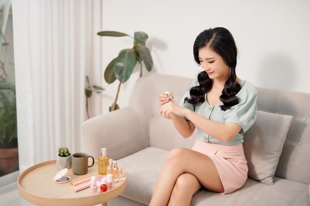 Красивая молодая женщина использует увлажняющую сыворотку против старения на руках