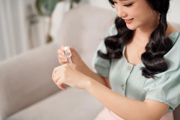 아름다운 젊은 여성이 그녀의 손에 모이스처 라이저 안티 에이징 세럼 트리트먼트를 사용하고 있습니다.