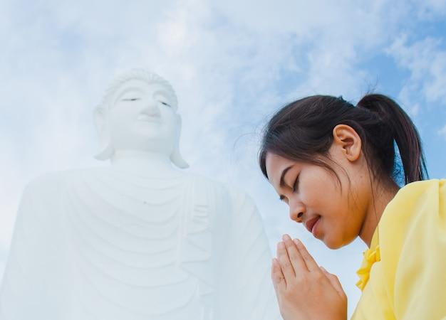 Beautiful young woman is worshiping the buddha.