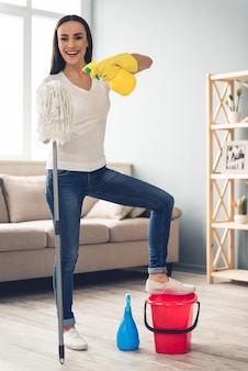 Beautiful young woman in jeans is holding a mop. cleaning concept