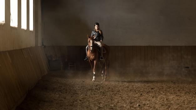 Красивая молодая женщина-жокей делает тренировку в манеже