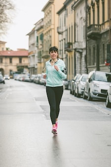 Beautiful young woman jogging alone in the city